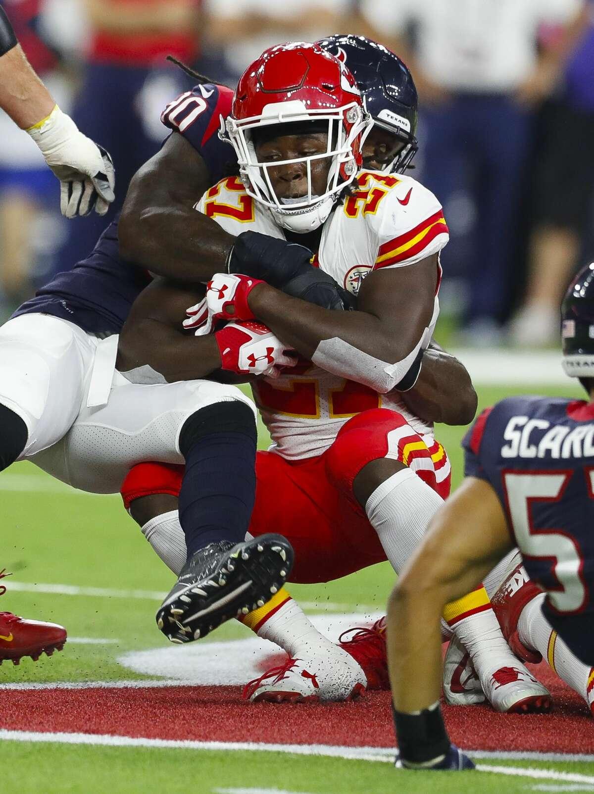 Kansas City Chiefs running back Kareem Hunt (27) is wrapped up by Houston Texans outside linebacker Jadeveon Clowney (90) during the first quarter of an NFL football game at NRG Stadium on Sunday, Oct. 8, 2017, in Houston. ( Brett Coomer / Houston Chronicle )