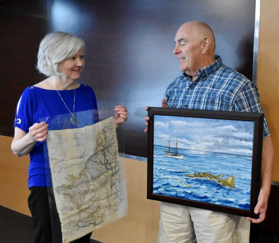 Linda Berkery of Latham shows the silk survival map that belonged to her father, William Styles. Her husband, Jack Berkery, displays his painting depicting the rescue of her father and other B-17 crew members in the North Sea in World War II. (Lois Dysard photo)