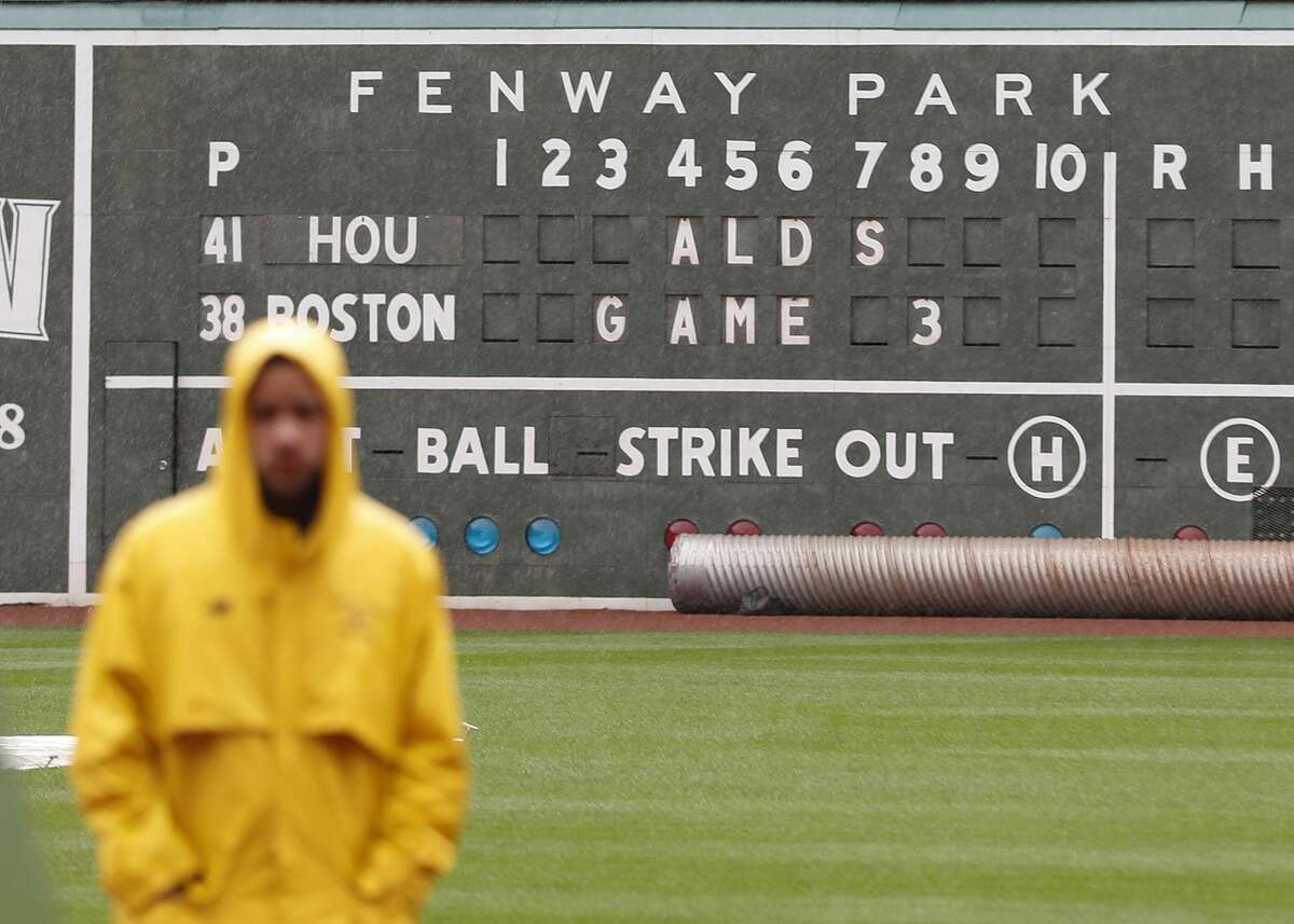 A guard stands in the rain on the field during a brief rainshower before the start of the ALDS Game 3 at Fenway Park, Sunday, Oct. 8, 2017, in Boston . ( Karen Warren / Houston Chronicle )