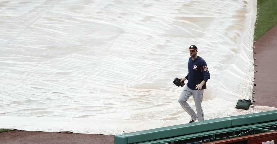 Houston Astros pitcher James Hoyt runs across the tarp during a brief rainshower before the start of the ALDS Game 3 at Fenway Park, Sunday, Oct. 8, 2017, in Boston .  ( Karen Warren / Houston Chronicle ) Photo: Karen Warren/Houston Chronicle