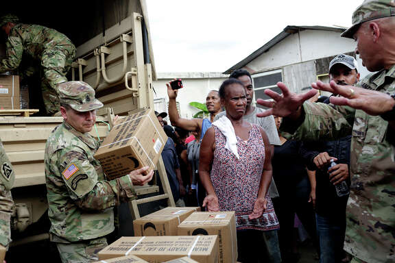 Residents of the San Isidro neighbor-hood, still living without electricity, pick up meals from the U.S. Army National Guard in Canovanas, Puerto Rico.