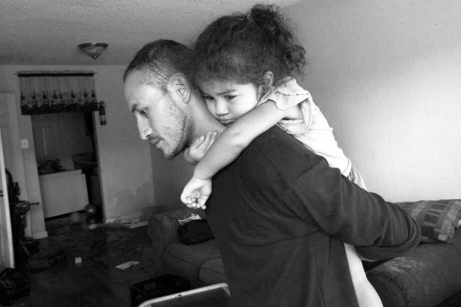 Byron Soto, 31, carries his daughter Kiara inside an apartment ruined by Hurricane Harvey's floodwaters.