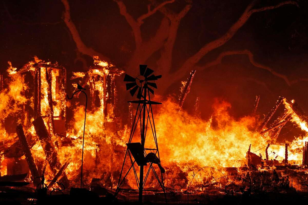A structure fire burns behind an ornamental windmill as a wild fire burned on Soda Canyon Road in Napa, Calif., on Monday, October 9, 2017.