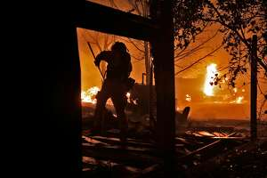 A firefighter removes debris as he protects one structure as another burns next door as a wild fire burned on Soda Canyon Road in Napa, Calif., on Monday, October 9, 2017.