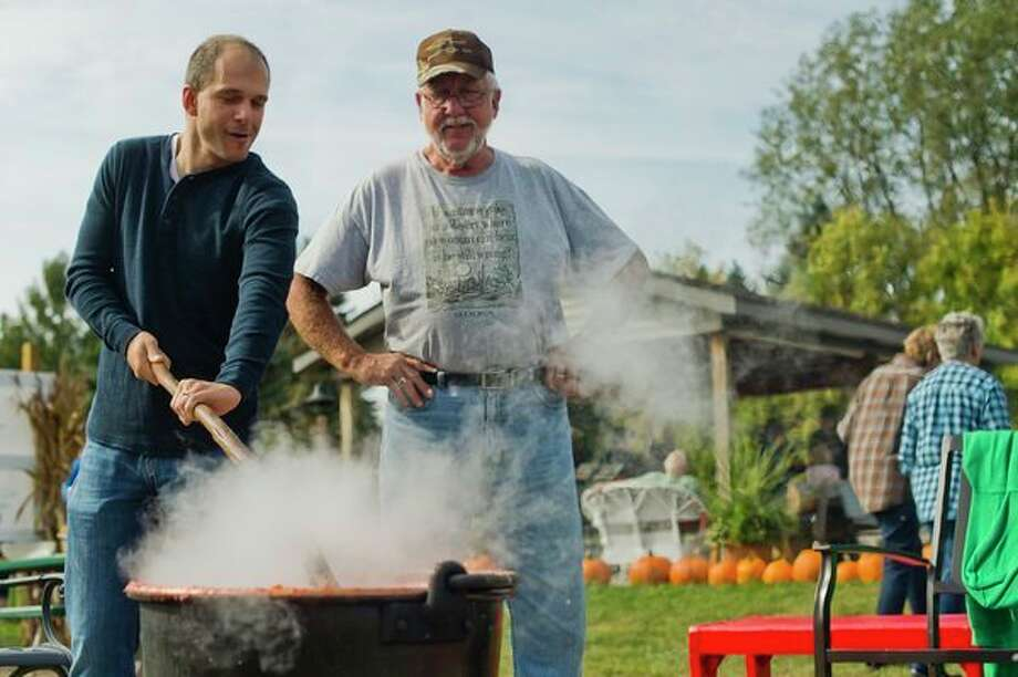Jay Rose of Midland, left, stirs a large pot of apple butter as Mike Deneke of Sanford watches during the annual Apple Butter Day at Apple Blossom Orchard on Saturday in Midland. The day provides visitors to the orchard a change to witness and even help in the process of producing apple butter. (Katy Kildee/kkildee@mdn.net)