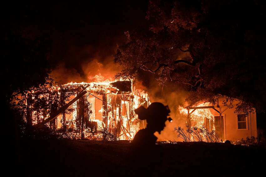 An inmate firefighter passes burning structures on Partrick Rd. in Napa, Calif., on Monday, Oct. 9, 2017.