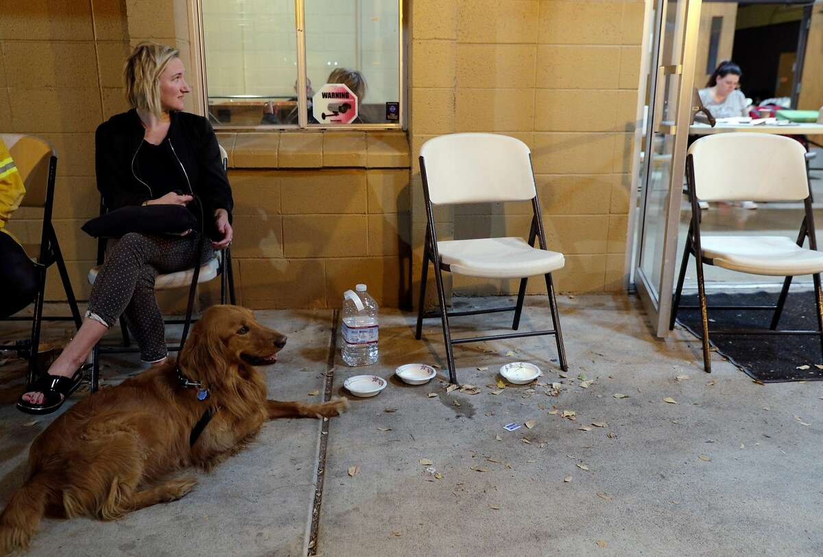 Magali Charmot looks in toward the Red Cross shelter with her dog Jax at Crosswalk Church in Napa, Calif., on Monday, October 9, 2017. Charmot was evacuated from her parents' house which she was housesitting when several large wildfires consumed several structures and threatened hundreds of others in Napa and Sonoma Counties.