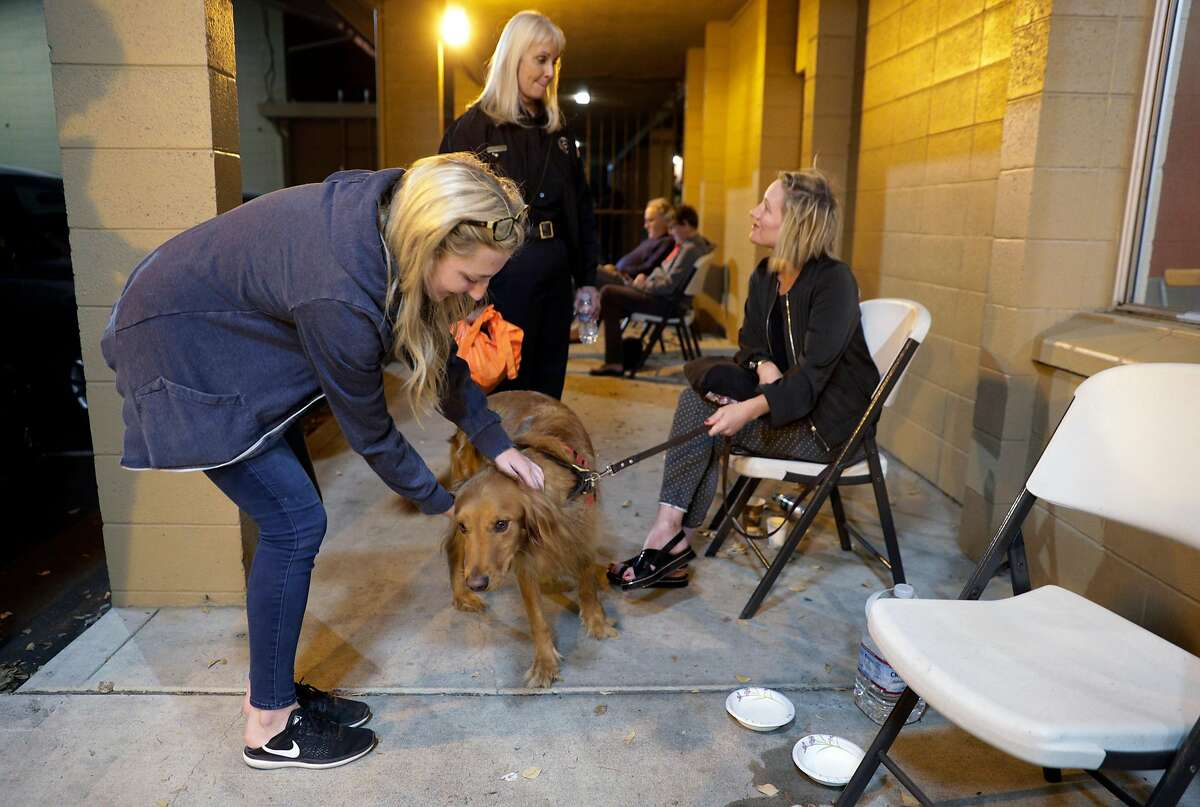 Emily Bernstein, left, pets Jax, as Jax's owner, Magali Charmot, speaks with Joanne Duncan, center, at Crosswalk Church in Napa, Calif., on Monday, October 9, 2017. Several large wildfires consumed several structures and threatened hundreds of others in Napa and Sonoma Counties.