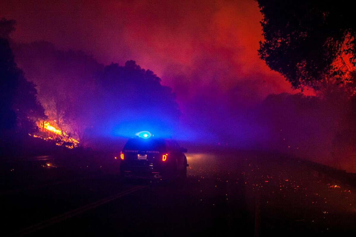 A California Highway Patrol vehicle navigates through the fire zone on Highway 12 during a wild fire in Napa, California on October 9, 2017.