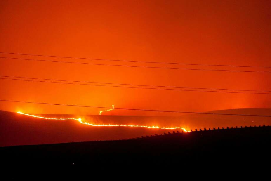 Flames moved through the vineyards as a fast moving wind whipped wild fire raged though the Napa/Sonoma wine region in Napa on Oct. 9, 2017.  Multiple fire that erupted in Napa, Sonoma, Calistoga and the Santa Rosa area have burned homes and wineries. Mandatory evacuations have be displaced hundreds of residents through out the area. Photo: Peter DaSilva, Special To The Chronicle