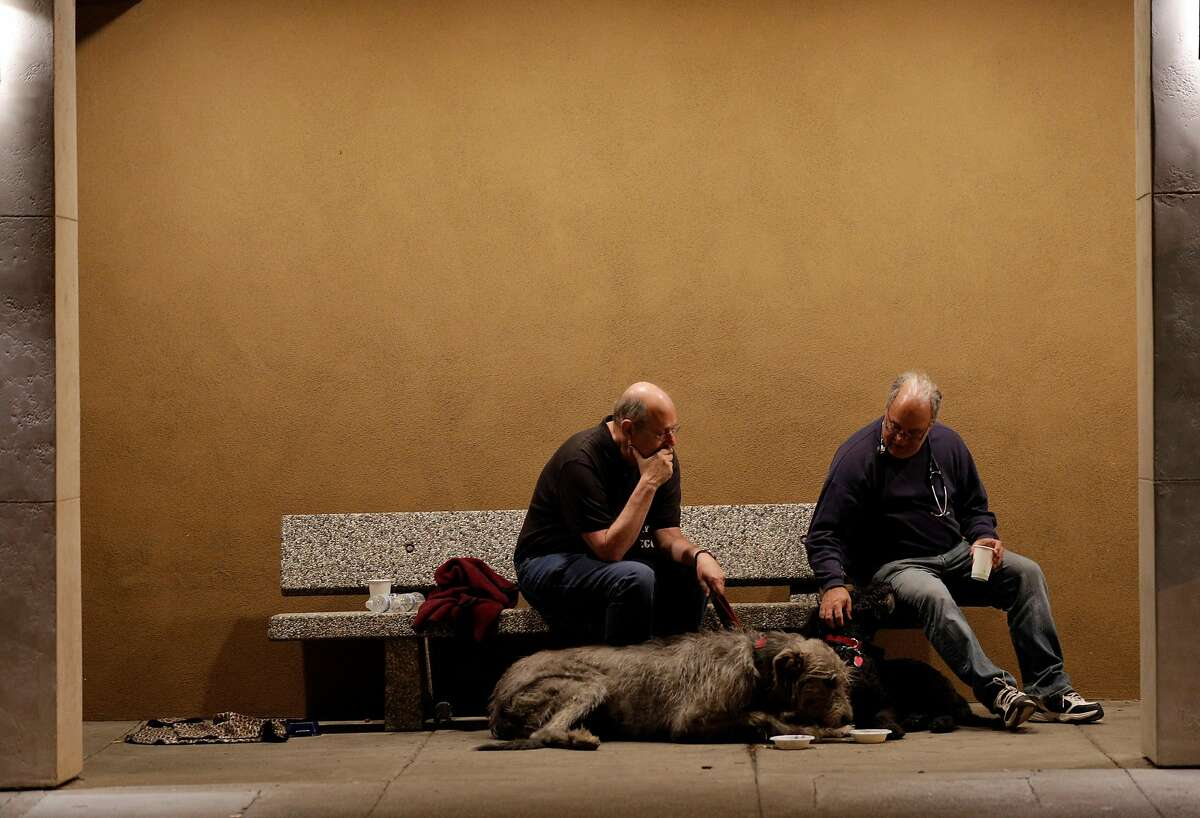 Peter Gennet sits with Dr. Larry Posner with Peter's dogs Quinn, and Rufus at Crosswalk Church after they were both evacuated from their homes in Napa, Calif., on Monday, October 9, 2017. Several large wildfires consumed several structures and threatened hundreds of others in Napa and Sonoma Counties.