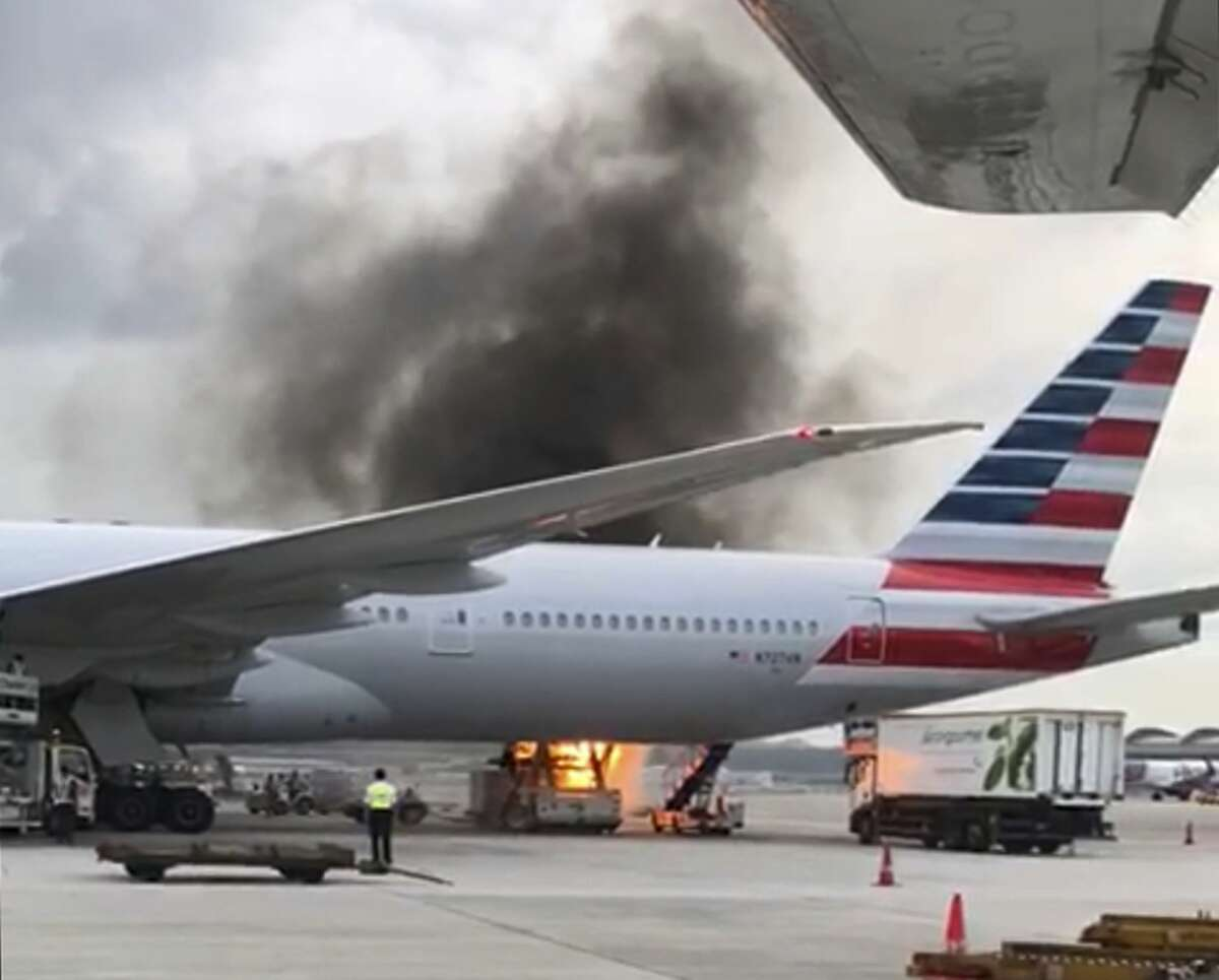 A fire breaks out on loading equipment in the process of loading an American Airlines jet at Hong Kong airport on Monday Oct. 9, 2017. A spokeswoman for the airline, Martha Thomas, said Monday the container that was on the loading equipment also caught fire in the process. She said the cargo it contained was