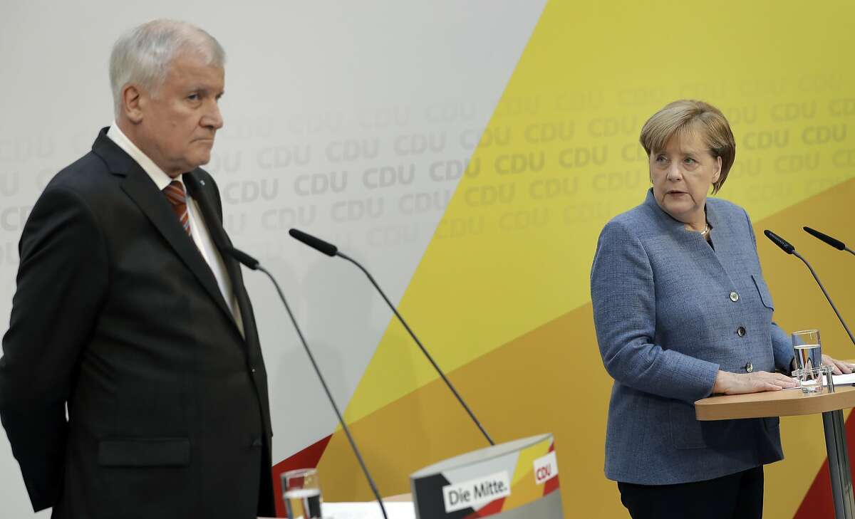 German Chancellor and Chairwomen of the German Christian Democratic Party (CDU), Angela Merkel, right, and the chairman of the German Christian Social Union Party (CSU), Horst Seehofer, left, address the media during a joint press conference at the CDU headquarter in Berlin, Germany, Monday, Oct. 9, 2017. Germany's conservative parties say they have agreed on a law limiting the number of migrants allowed to enter the country every year. (AP Photo/Michael Sohn)
