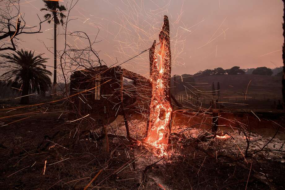 Embers dart from what's left of a tree at the Nicholson Ranch Winery in Sonoma during the morning hours of Oct. 9. Photo: Noah Berger, Special To The Chronicle
