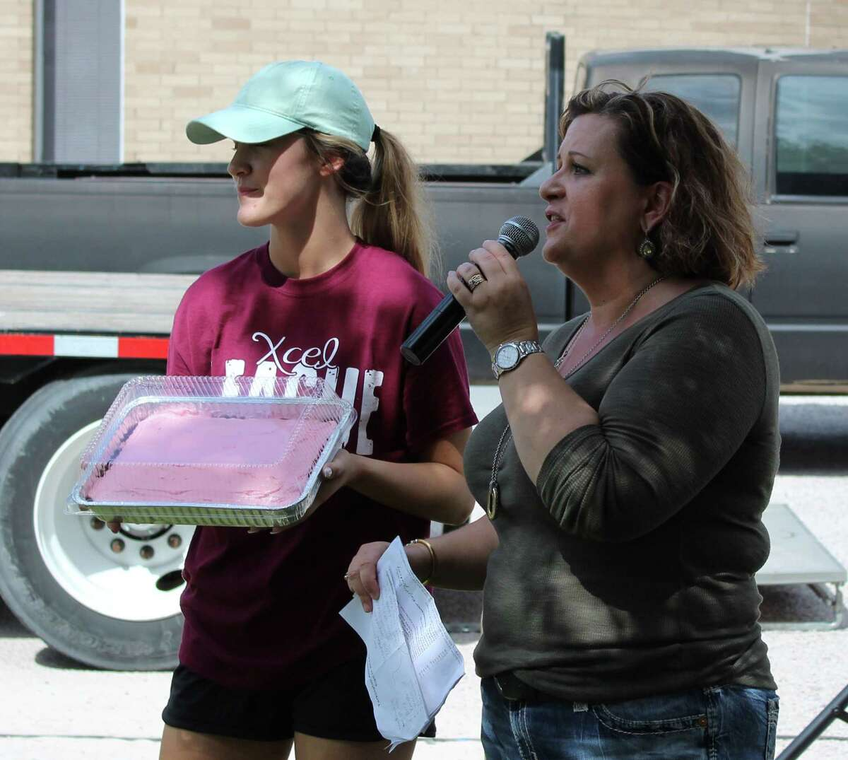 Mollie Lambert (right) of the Tarkington ISD Education Foundation auctions off a strawberry cake displayed by Tarkington High School student Becca Rasberry (left).