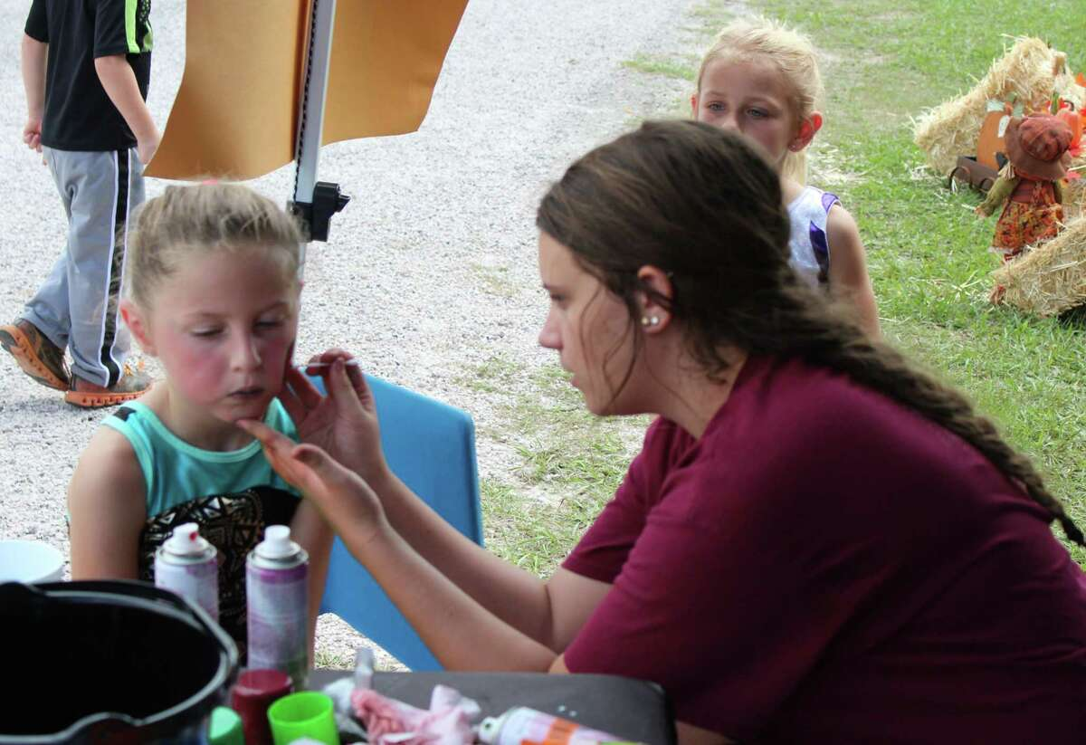 Jaci Wolcik (right) engages in some face painting for Addison Newton (left) at Tarkington Roundup.