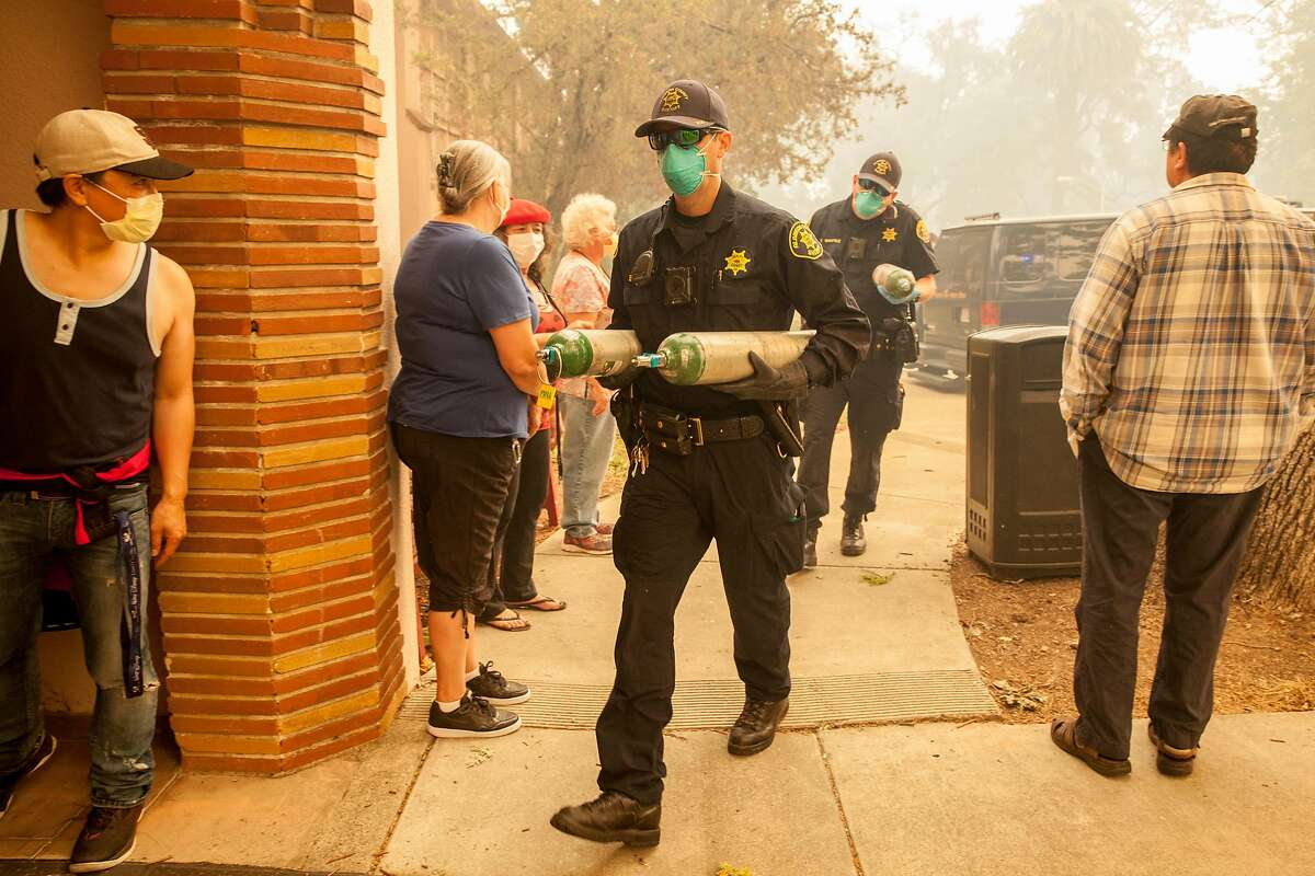 Alameda County Sheriff deputies carry in oxygen tanks to one of the wards at the Sonoma Developmental Center to help evacuate clients under a mandatory evacuation order for the whole facility as fire threatens the town of Glen Ellen, Calif., on Oct 9, 2017. Multiple fires that erupted in Napa, Sonoma, Calistoga and the Santa Rosa area have burned homes and wineries.