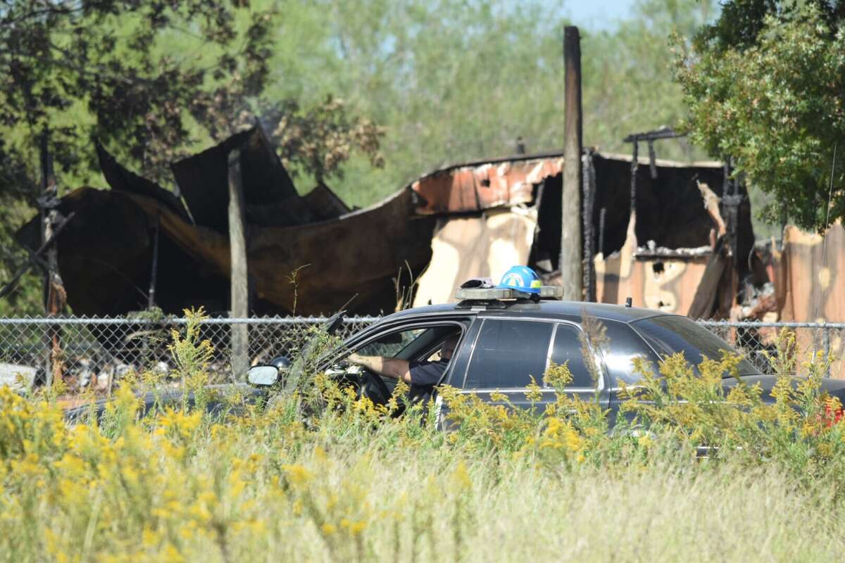 Arson investigators and firefighters comb over the remains of a mobile home in Seguin, Texas, that authorities believe was intentionally set ablaze in a murder-suicide.