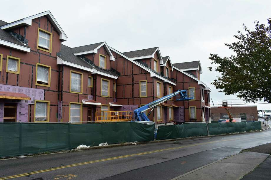 Washington Village — On a rainy Monday in early October 2017 in Norwalk, Conn., construction pauses at 13 Day St.at the Hanford Place Building A component of the Washington Village development of Trinity Financial. Hanford Place Building A will total 10 apartments, four of them with four bedrooms apiece and the remainder split between two- and three-bedroom units. Going vertical across the street is the larger Building B element of the project at 20 Day St., which will encompass 70 units. Photo: Alexander Soule / Hearst Connecticut Media / Stamford Advocate