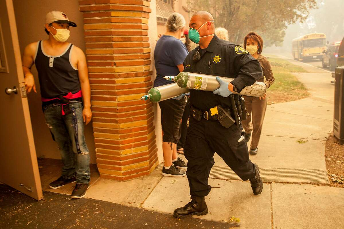Alameda County Sheriff deputy carries in oxygen tanks to one of the wards at the at the Sonoma Developmental Center during a mandatory evacuation as the Tubbs Fire threatens the town of Glen Ellen, Calif. on Monday, Oct. 9, 2017.