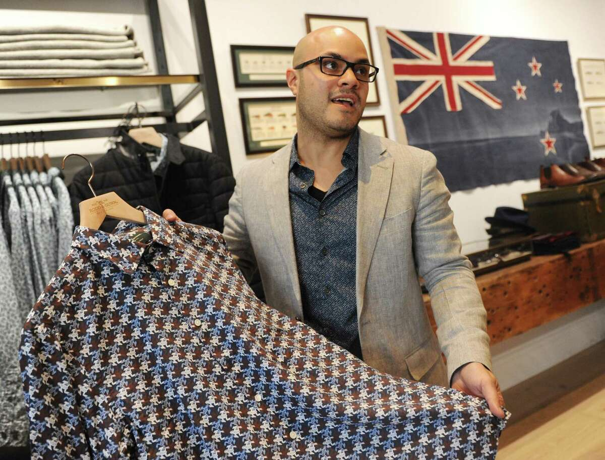 Store manager Marc Marranzino shows the pattern of a Liberty shirt, custom-designed for Rodd & Gunn, at the New Zealand-based men's clothing store Rodd & Gunn along Greenwich Avenue in Greenwich, Conn. Wednesday, Oct. 4, 2017.