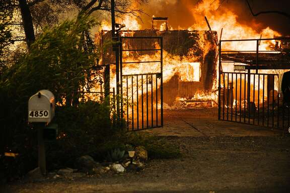 A house is seen engulfed in flames on Saddle Club Lane in Santa Rosa, Calif. Monday, October 9, 2017.