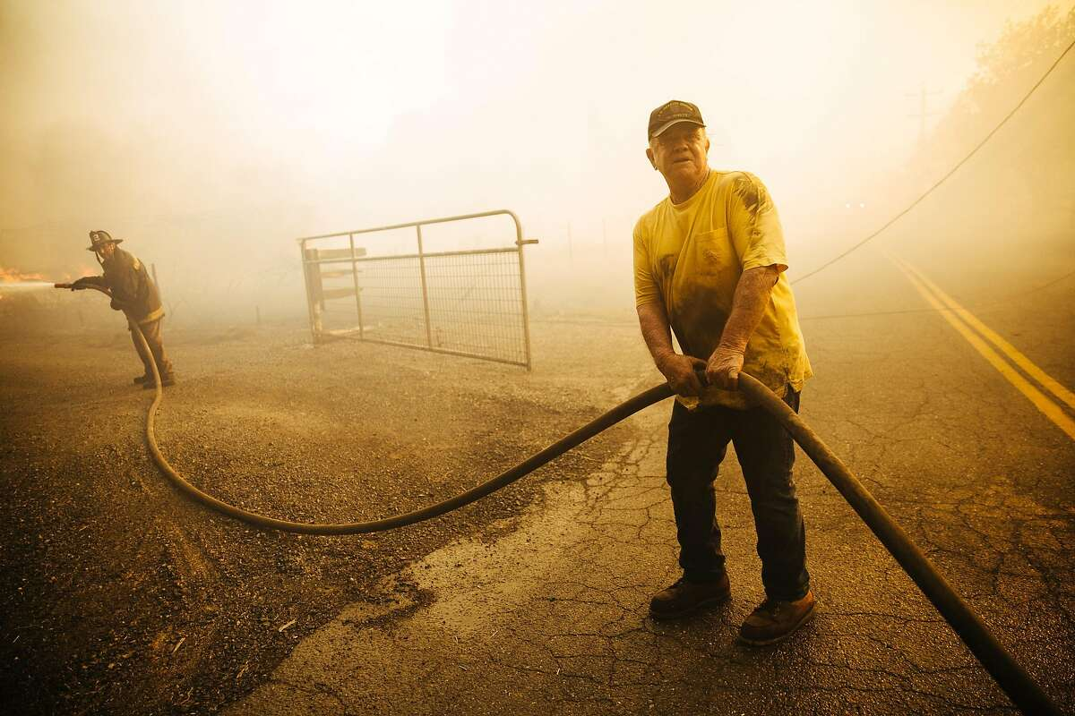 Firefighter Derick O'?'Leary (left) and Danny Dortch help battle blazes on Baird Road in Santa Rosa on Oct. 9.