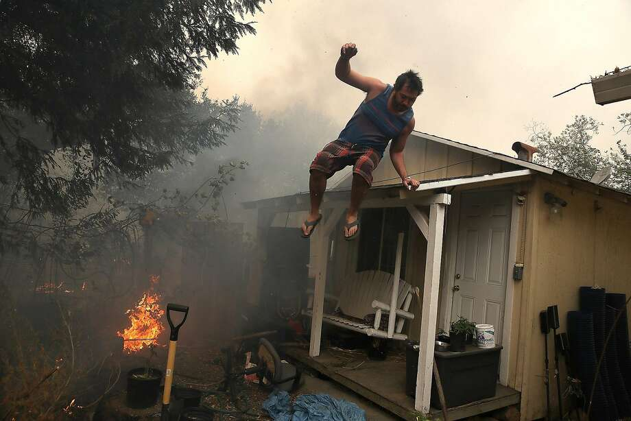 A resident rushes to save his home as an out of control wildfire moves through the area on October 9, 2017 in Glen Ellen, California. Tens of thousands of acres and dozens of homes and businesses have burned in widespread wildfires that are burning in Napa and Sonoma counties.  (Photo by Justin Sullivan/Getty Images) Photo: Justin Sullivan, Getty Images