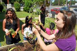 Tiffany Torres, a service member from Common Grounds Schools' Food Corps, helps children in the Casa Otonal summer program plant a community garden.