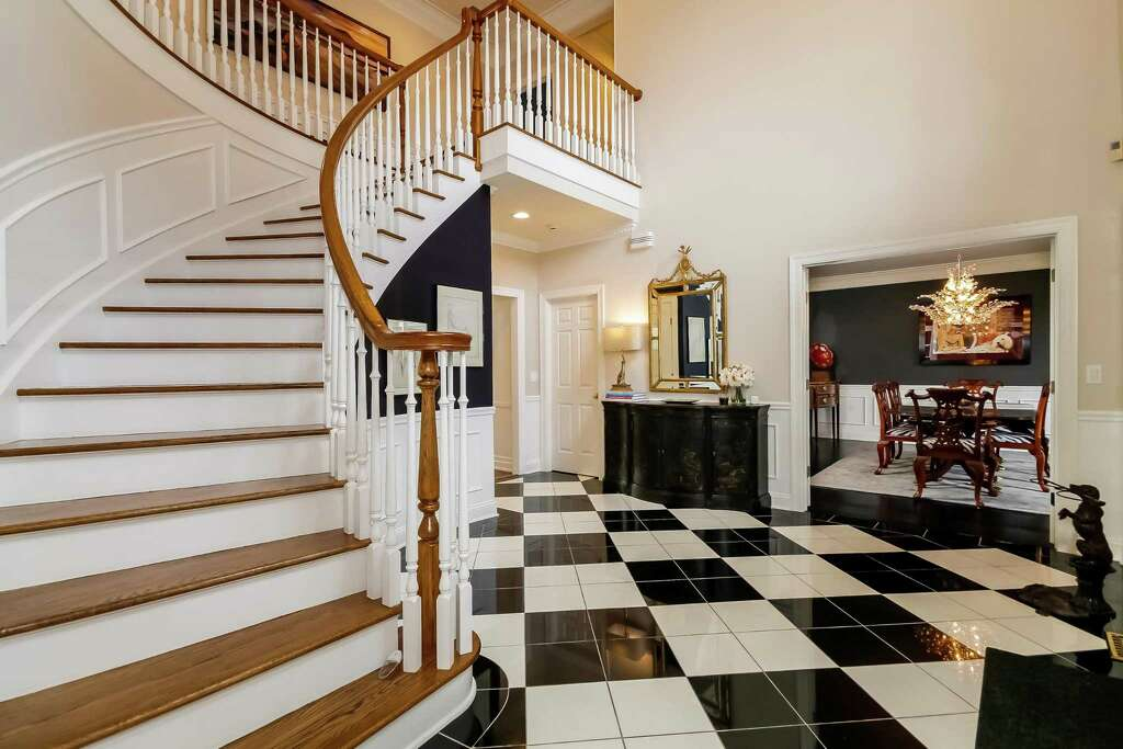 In The Two Story Entry Foyer Flooring Comprises Black Granite And White Glassos Quartzite