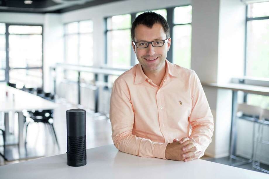 "Kayak Chief Scientist poses with an Amazon Echo device, which features the Alexa voice assistant. Kayak users can now make hotel bookings with Alexa's Kayak ""skill."" Photo: Contributed Photo /Scott Gries"