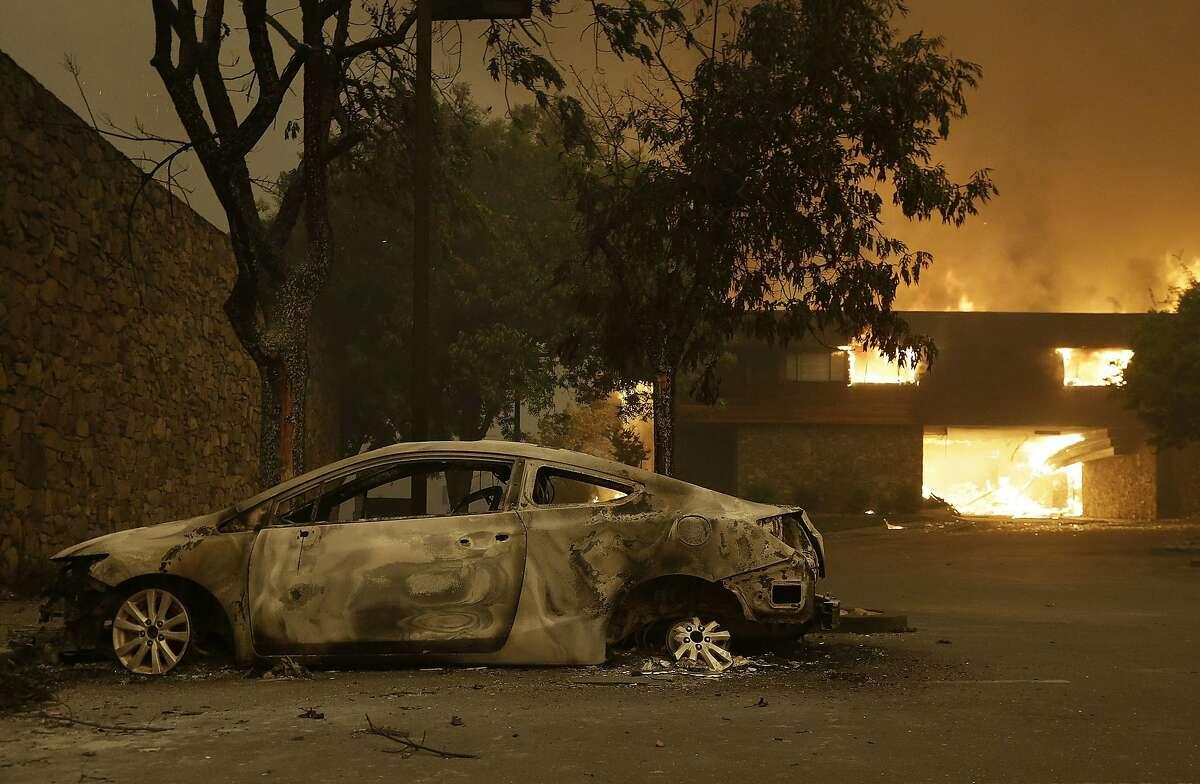 The remains of a car sits near the Fountaingrove Inn Hotel as it burns at rear in Santa Rosa, Calif., Monday, Oct. 9, 2017. (AP Photo/Jeff Chiu)