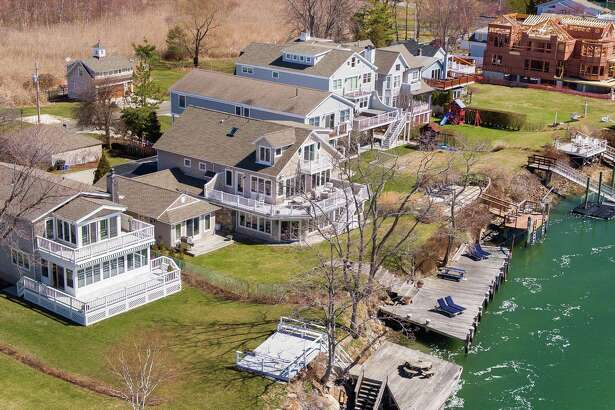 The shingle colonial house at 334 Pine Creek Avenue has its own dock/mooring, an attached guest cottage, access to a private neighborhood beach, and beautiful views of Long Island Sound.