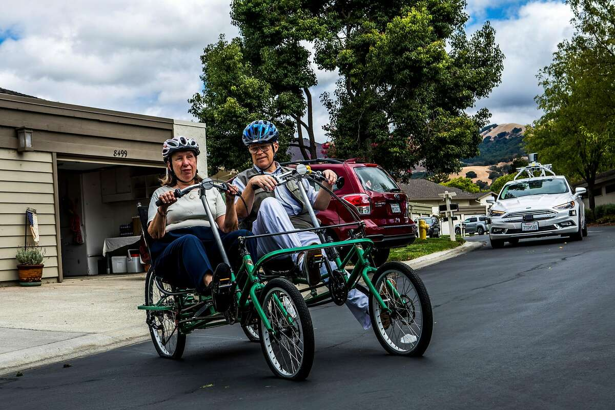 Bev and Victor Clifford get around by dual bicycle in the Villages Golf and Country Club in San Jose, Calif., Sept. 20, 2017. Behind them is one of the autonomous cars which Voyage operates on a loop within the retirement village, offering rides to residents. (Christie Hemm Klok/The New York Times)