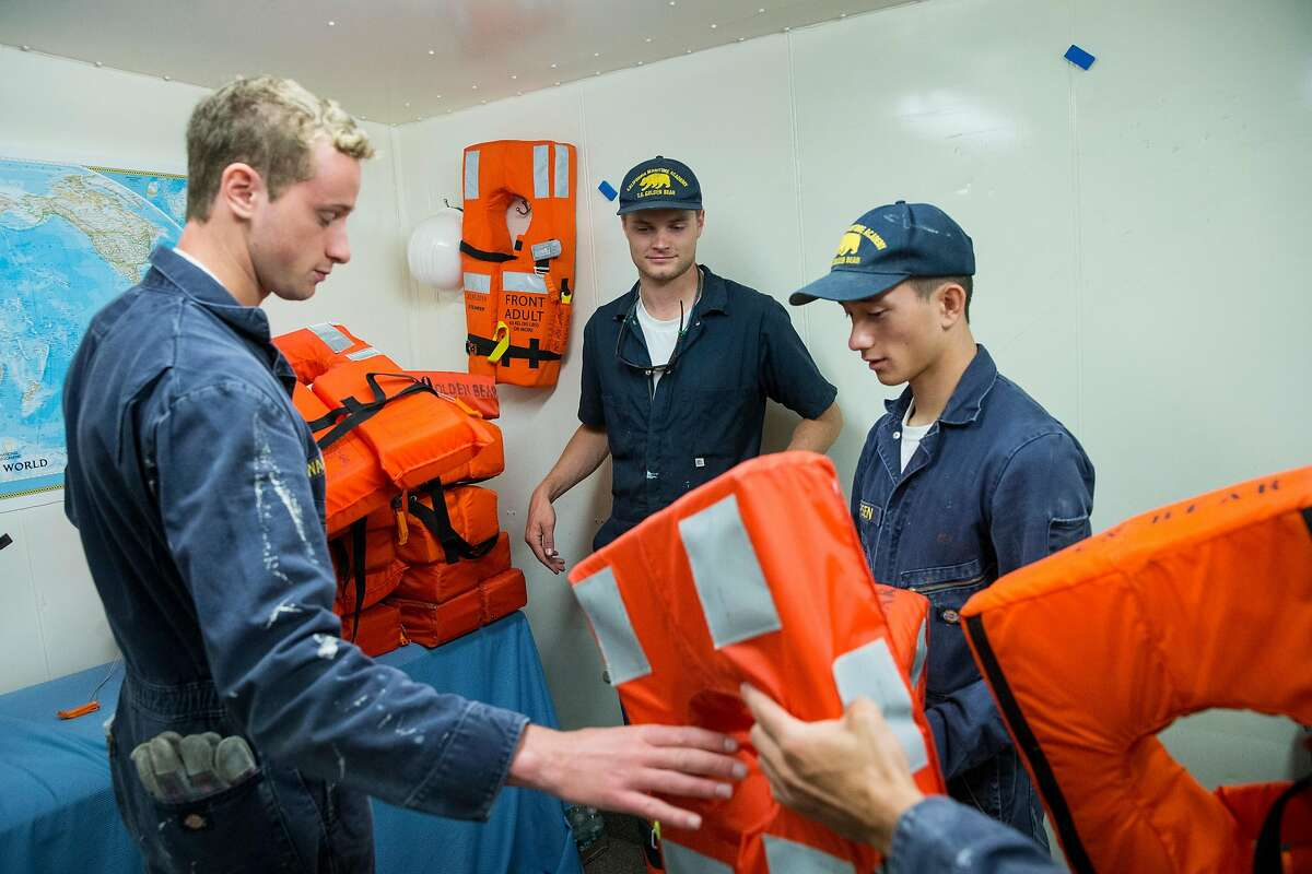 Goody Walowit, Colby White and Joseph Jepsen (left to right) arrange life jackets while preparing the training ship Golden Bear for homecoming weekend visitors at the California State University Maritime Academy in Vallejo, Calif., on Monday, October 2, 2017. The university is the only degree-granting maritime university in the West.