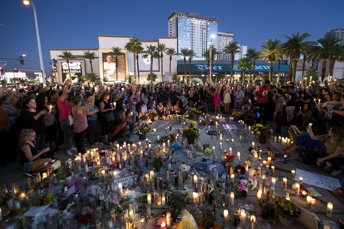 LAS VEGAS, NV - OCTOBER 8: Mourners hold their candles in the air during a moment of silence during a vigil to mark one week since the mass shooting at the Route 91 Harvest country music festival, on the corner of Sahara Avenue and Las Vegas Boulevard at the north end of the Las Vegas Strip, on October 8, 2017 in Las Vegas, Nevada. On October 1, Stephen Paddock killed 58 people and injured more than 450 after he opened fire on a large crowd at the Route 91 Harvest country music festival. The massacre is one of the deadliest mass shooting events in U.S. history. (Photo by Drew Angerer/Getty Images) *** BESTPIX ***
