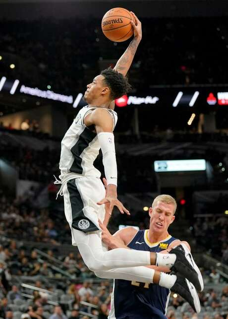 San Antonio Spurs' Dejounte Murray, left, dunks over Denver Nuggets' Mason Plumlee during the second half of a preseason NBA basketball game, Sunday, Oct. 8, 2017, in San Antonio. Photo: Darren Abate /AP Photo