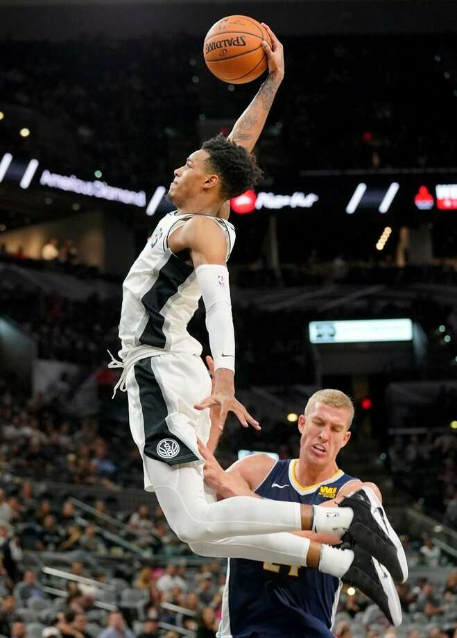 San Antonio Spurs' Dejounte Murray, left, dunks over Denver Nuggets' Mason Plumlee during the second half of a preseason NBA basketball game, Sunday, Oct. 8, 2017, in San Antonio. Photo: Darren Abate /AP Photo