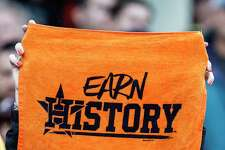 "A Houston Astros fan holds up an ""Earn History"" towel during the ninth inning of Game 4 of the ALDS against the Boston Red Sox at Fenway Park on Monday, Oct. 9, 2017, in Boston."
