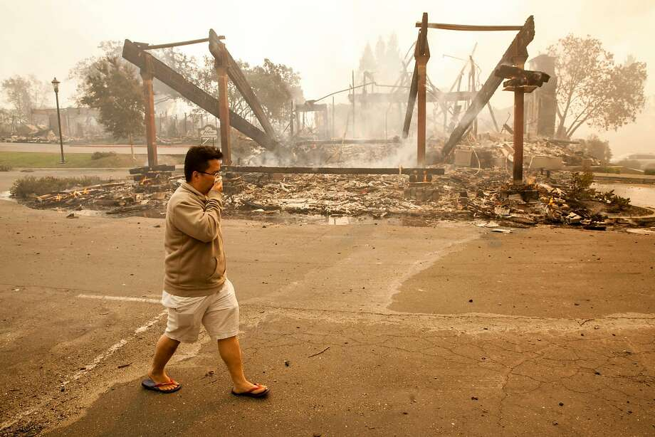 A visitor from Malaysia who was staying at the Hilton Hotel in Santa Rosa walks past the remains of the building. Photo: Peter DaSilva, Special To The Chronicle