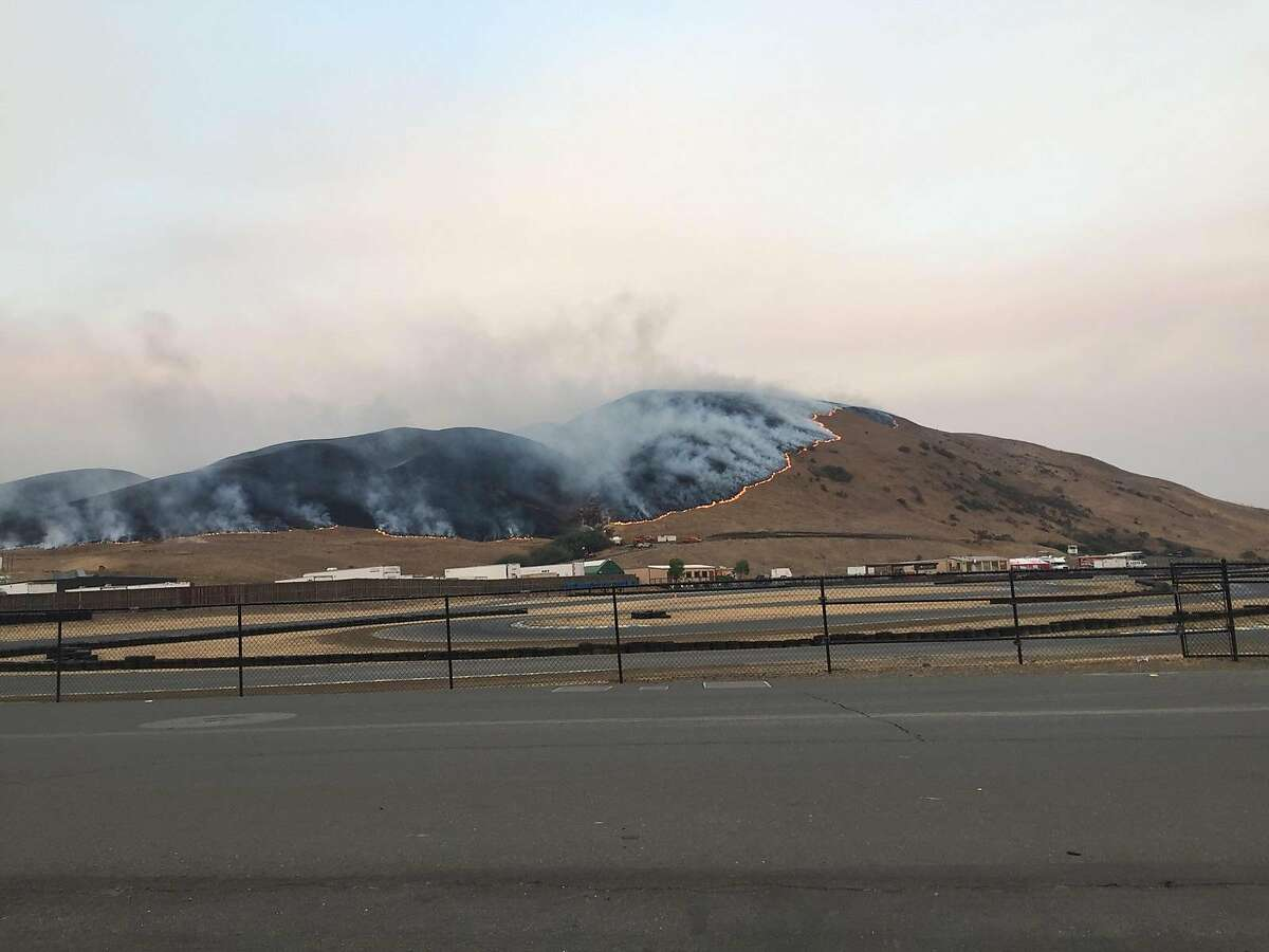 A wildfire is seen advancing along Cougar Mountain above Sonoma Raceway, leaving a charred hillside behind.