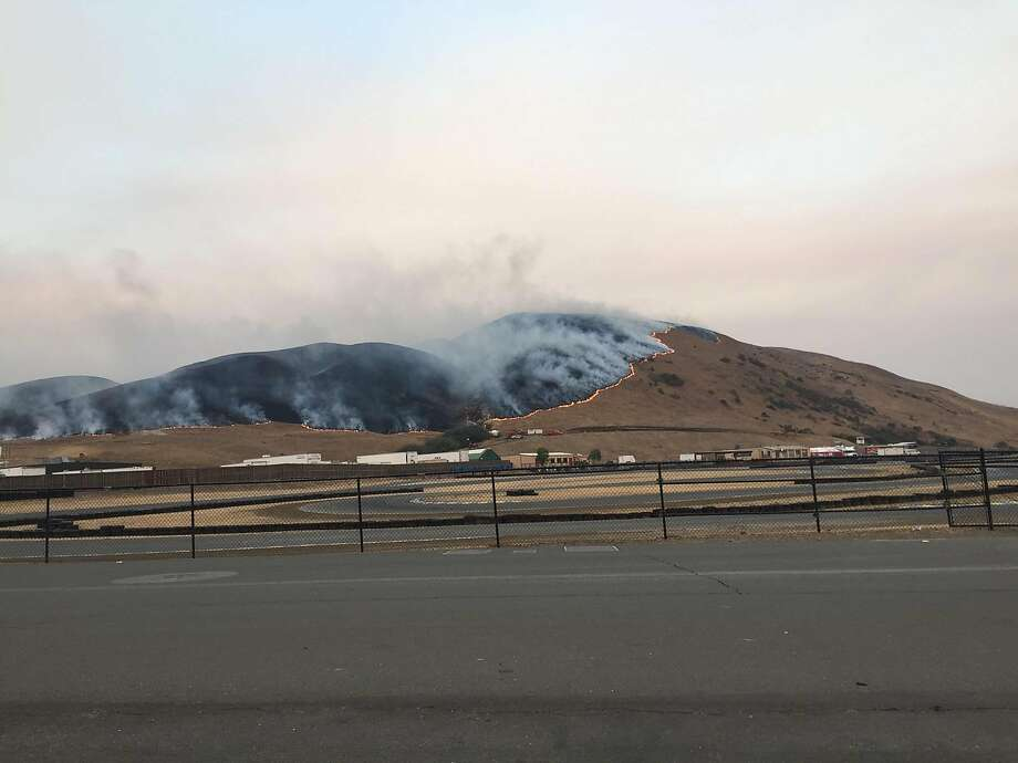 A wildfire is seen advancing along Cougar Mountain above Sonoma Raceway, leaving a charred hillside behind. Photo: Photo Courtesy Sonoma Raceway