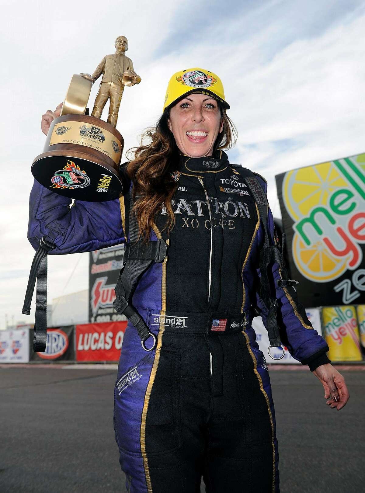 In this photo submitted by the NHRA, Alexis DeJoria celebrates her first career NHRA drag race for the Funny Car victory, Sunday, Feb. 23, 2014, in Chandler, Ariz. She is the 14th female driver to win an NHRA Mello Yello Series race and the fourth to do it in Funny Car. (AP Photo/NHRA, Jerry Foss)