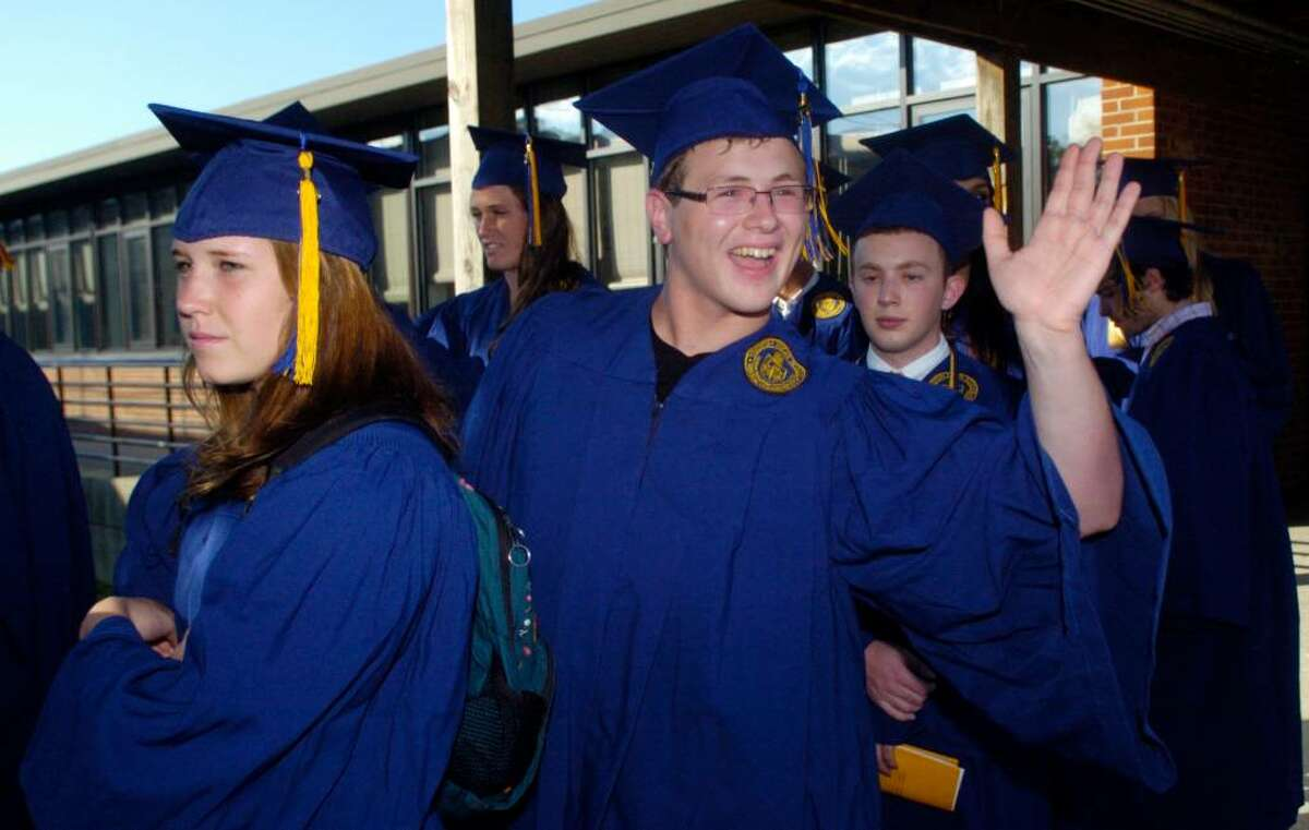 Travis James waves to friends as he walks in the processional to begin the Weston High School graduation ceremony at the school on Thursday, June 24, 2010.
