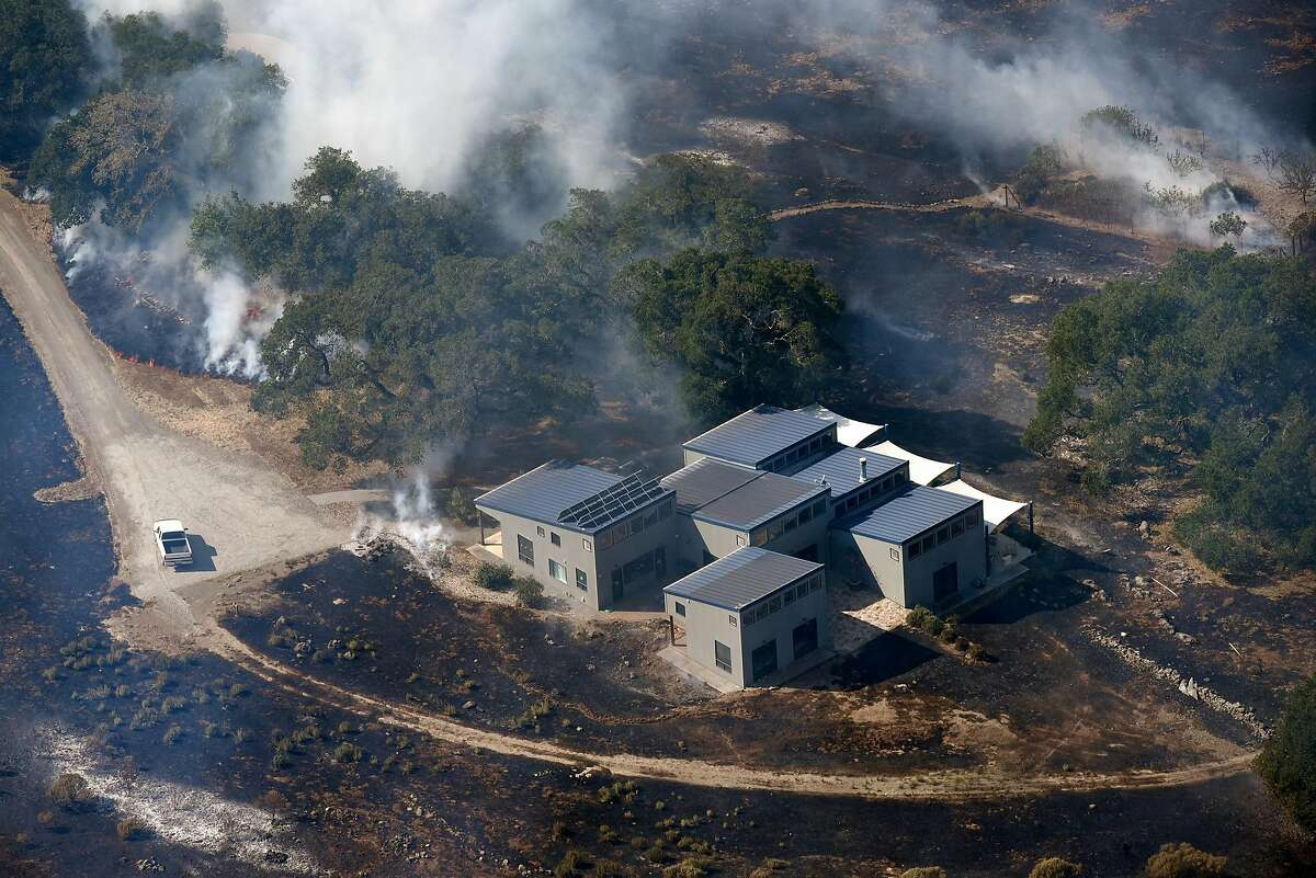The Atlas fire burns near a structure in the hills East of downtown Napa, Calif., on Monday, October, 9, 2017.