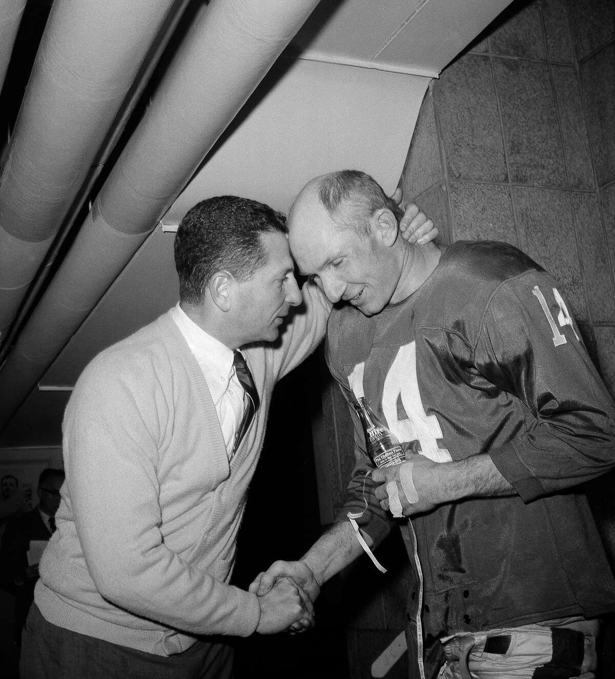 FILE - In this Dec. 15, 1963, file photo, New York Giants coach Allie Sherman, left, congratulates his quarterback, Y. A. Tittle, after defeating the Pittsburgh Steelers in a football game at Yankee Stadium in New York. Tittle, the Hall of Fame quarterback and 1963 NFL Most Valuable Player, has died. He was 90. His family confirmed to LSU, where Tittle starred in college, that he passed away. No details were immediately provided. (AP Photo)
