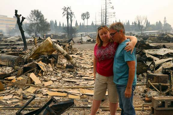 Dana Walter puts her arm around a friend, Richard Snyder, whose home at the Journey�s End Mobile Home Park burned in a wildfire, in Santa Rosa, Calif., Oct. 9, 2017. Fast-moving wildfires raged across several counties in Northern California overnight, forcing the evacuation of at least two hospitals and numerous neighborhoods early Monday, the authorities said. (Jim Wilson/The New York Times)