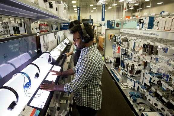 Prithvi Raj Aare, a University of Houston student, tests wireless headphones at the Best Buy on Richmond Avenue.