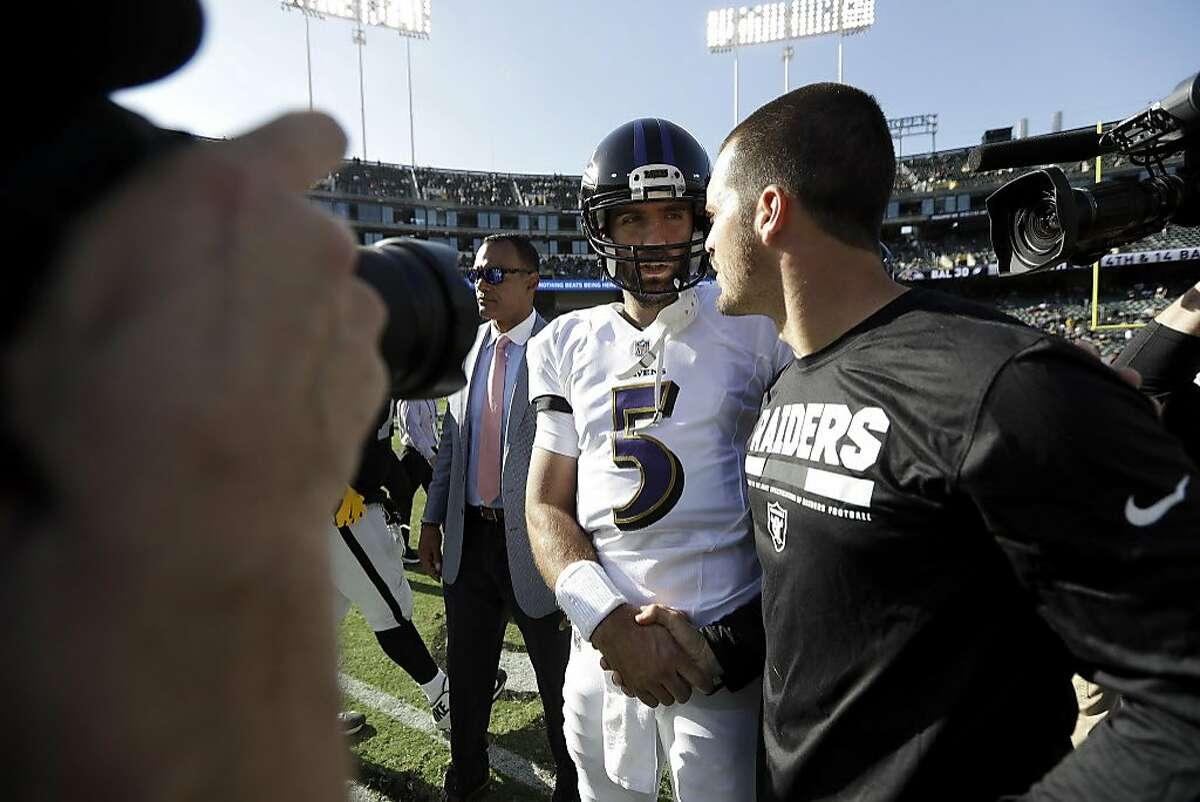 Baltimore Ravens quarterback Joe Flacco (5) greets injured Oakland Raiders quarterback Derek Carr after an NFL football game in Oakland, Calif., Sunday, Oct. 8, 2017. The Ravens won 30-17. (AP Photo/Marcio Jose Sanchez)