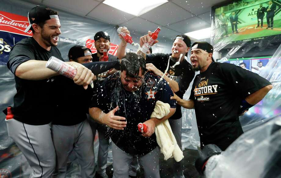 Astros relievers Chris Devenski and James Hoyt spray champagne on bullpen coach Criag Bjornson in the clubhouse after the Astros beat Boston Red Sox 5-4 in the ALDS Game 4 at Fenway Park, Monday, Oct. 9, 2017, in Boston . Photo: Karen Warren, Houston Chronicle / @ 2017 Houston Chronicle